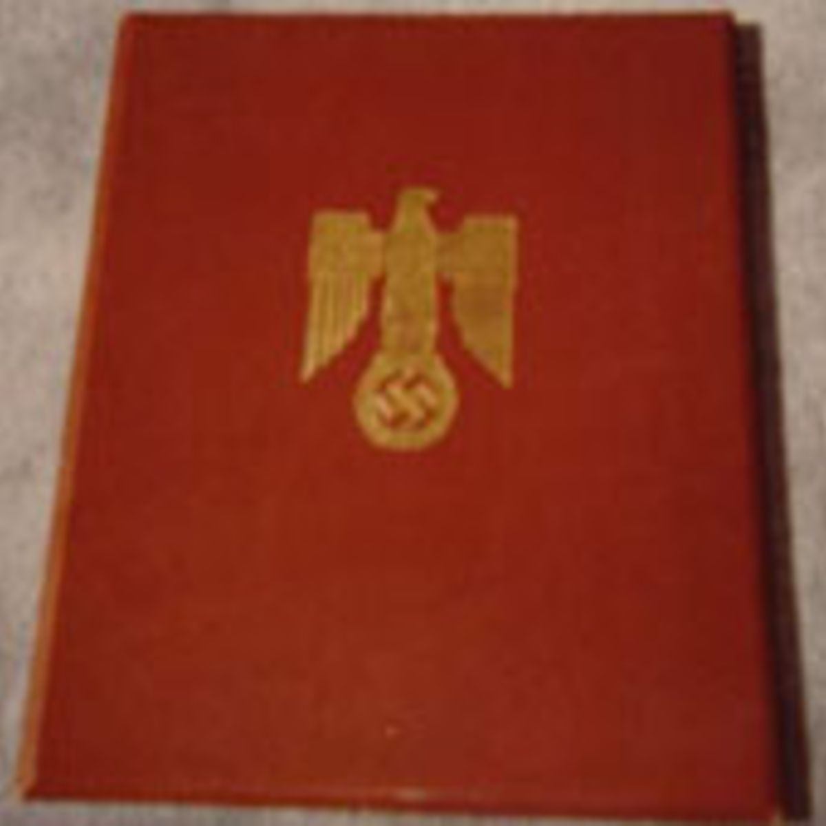 NAZI KNIGHTS CROSS OF THE IRON CROSS DOCUMENT--PARCHMENT DOUBLE PAGE DOCUMENT. AWARD FOLDER IS RED LEATHER WITH GOLD EMBOSSED EAGLE ON FRONT.